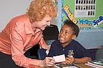 Second grade black girl smiles broadly accepting reward from red headed white teacher