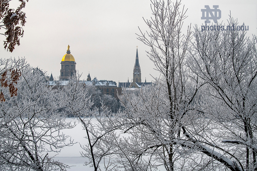 February 17, 2021; The Main Building framed by trees covered with frost around St. Joseph Lake. (Photo by Barbara Johnston/University of Notre Dame)