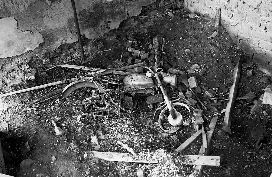A motorbike lies under the burnt out house of family members of Adem Jashari, KLA military leader killed during the Kosovo war.
