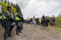 Pictured: A group of young people walk in front of a line of police officers who surrounded a van used to transport sound equipment which was confiscated. Monday 31 August 2020<br /> Re: Around 70 South Wales Police officers executed a dispersal order at the site of an illegal rave party, where they confiscated sound gear used by the organisers in woods near the village of Banwen, in south Wales, UK.