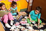 Education Preschool 3-4 year olds one girl working on floor puzzle as two others look at books
