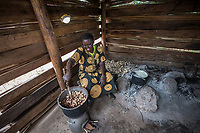 Uganda, Butema. Milly Mugisa (53), uses a Biolite stove at her home, it charges a light and charges her mobile phone. Cooking at home in her kitchen with the Biolite stove.