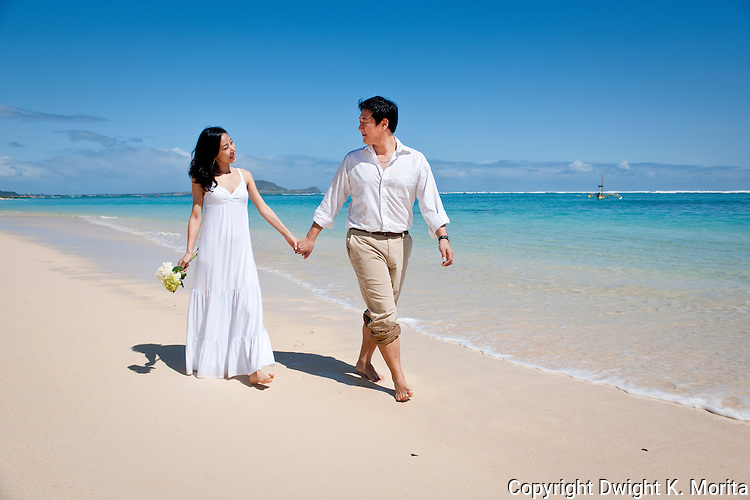 Asian bride and groom stroll hand in hand on Lanikai beach as the couple celebrate their marriage.