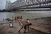 A garbage collector picks up plastic cups on the ghats of river Hooghly in Howrah, Kolkata, West Bengal  on Friday, May 26, 2017. Photographer: Sanjit Das