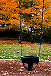 An empty swings hangs lonesomely in the park after summer has gone.