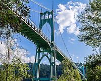 St Johns Bridge is a steel suspension bridge that spans the Willatte River in Portland, OR. Towers are 408 feet and a length of 2067 feet. The is a view from Cathedral Park on a Spring day with blue skies over the Portland hills.
