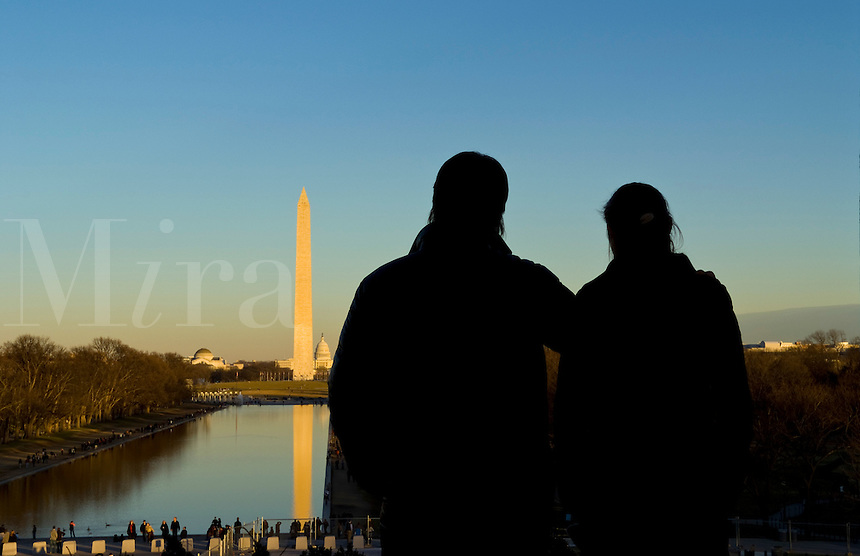 Tourist couple at beautiful tall tower of the Washington Monument and pond with capital building at sunset in Washington DC USA