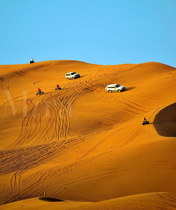 Four wheel drive vehicles and quadbikes drive in the desert. Dubai. United Arab Emirates.