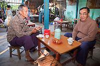 Myanmar, Burma.  Two Men Enjoying Breakfast Tea.  Bagan Market Cafe.