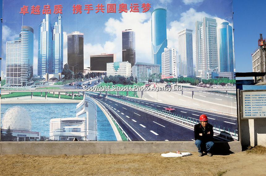A Chinese worker has a rest in front of a billboard of CSCEC (China State Construction Engineering Corporation), one of Fortune Global 500 Corporations,  in Beijing, China..