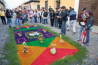 Antigua, Guatemala. Pedestrians admiring an alfombra (carpet) of colored sawdust, pine needles, and fresh fruits decorating the street in advance of the passage of a procession during Holy Week, La Semana Santa.  The alfombra will be finished only a couple of hours before the passage of the procession, after which the remains will be quickly swept away by municipal street sweepers.