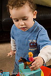 2 year old toddler boy at home playing with toys human people figure and animals vertical placing them on top of block box vertical