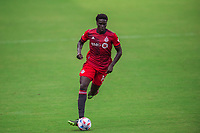 ORLANDO, FL - APRIL 24: Noble Okello #14 of Toronto FC dribbles the ball during a game between Vancouver Whitecaps and Toronto FC at Exploria Stadium on April 24, 2021 in Orlando, Florida.