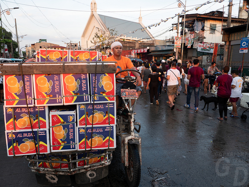 Street Photography, Manila, Philippines Street scene during Good Friday, Easter in Tondo, Transporting goods on a very unusual vehicle that is home made during Good Friday among a Easter parade