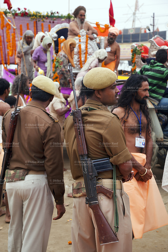 "India. Uttar Pradesh state. Allahabad. Maha Kumbh Mela. Seers and guru are seated on a trailer pulled by a tractor during a procession in Sangam under the police's supervision on the day of Mauni Amavasya Snan (Royal bath for Dark moon). The ritual ""Royal Bath"" is timed to match an auspicious planetary alignment, when believers say spiritual energy flows to earth. The Kumbh Mela, believed to be the largest religious gathering is held every 12 years on the banks of the 'Sangam'- the confluence of the holy rivers Ganga, Yamuna and the mythical Saraswati. The belief is that bathing and taking a holy dip will wash and free one from all the past sins, get salvation and paves the way for Moksha (meaning liberation from the cycle of Life, Death and Rebirth). The Maha (great) Kumbh Mela, which comes after 12 Purna Kumbh Mela, or 144 years, is always held at Allahabad. Uttar Pradesh (abbreviated U.P.) is a state located in northern India. 10.02.13 © 2013 Didier Ruef"