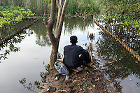"""A man fishing in a mangrove forest in the north-west of Jakarta. According to the Jakarta Post, """"it is now only a matter of time before mangroves are totally erased from the map of Jakarta — a victim of unbridled urbanization and industrialization programs initiated by the government""""."""
