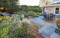 Small space stone, flagstone patio backyard garden with drought tolerant perennials, Lundstrom Garden, design by Susan Morrison