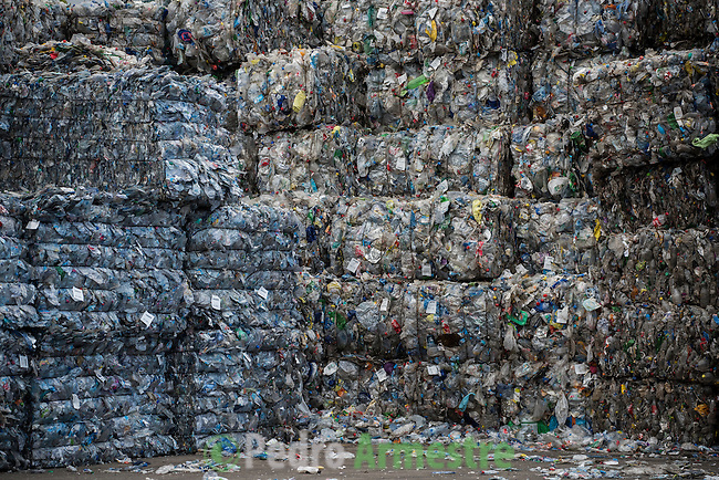 """A picture taken on November 3, 2015 shows stacks of plastic waste collected in the sea by fishermen at a plastic processing plant in Chiva, near Valencia. Ecoalf, a Spanish Madrid-based firm founded in 2010, has already launched """"a new generation"""" of clothes and accessories made from plastic bottles, old fishing nets and used tires found on land.  © Pedro ARMESTRE"""