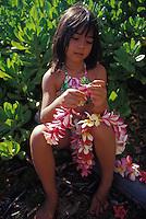 Young local Hawaiian girl making plumeria Leis of red, white, and pink flowers, Waialua, Hawaii.