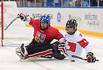 Sochi, RUSSIA - Mar 11 2014 -  Derek Whitson protects the puck from a Czech player as Canada takes on Czech Republic in Sledge Hockey at the 2014 Paralympic Winter Games in Sochi, Russia.  (Photo: Matthew Murnaghan/Canadian Paralympic Committee)