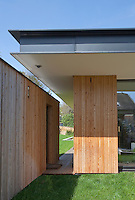 The construction of the house incorporates a metal roof with walls clad in natural pine