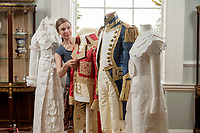 BNPS.co.uk (01202) 558833<br /> Pic: ZacharyCulpin/BNPS<br /> <br /> Pictured: Artist Stephanie Smart with the incredible paper outfits. (From left) A Regency 'walking dress' complete with a high necked spencer jacket, a coat inspired by Napoleon, an early 19th century British naval uniform and a another Regency walking dress<br /> <br /> A textile artist has unveiled a collection of remarkable Regency outfits she has painstakingly made out of paper.<br /> <br /> Stephanie Smart has produced 11 life-sized outfits including a red frockcoat modelled on the style of Napoleon.<br /> <br /> Others depict walking dresses, naval uniforms and spencer jackets from the Regency era. (1795-1837)<br /> <br /> Her creations are on display as part of an exhibition titled The Regency Wardrobe at Firlie Place in East Sussex.