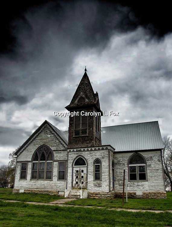 An old church stands in front of cloudy skies.