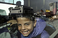 Pictured: A young boy smiles from the bus that takes him to the migrants camp Monday 08 Fabruary 2016<br /> Re: Migrants wait in the Piraeus passenger station to be transported to the migrants' camp in Elliniko, Athens, Greece