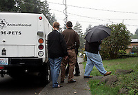Walk of Shame:: The owner of Lucky, a dog who has been locked in a basement for four years, then left without anyone home for the past three months, hides from the TV cameras under an umbrella after loading Lucky into a King County Animal Control truck outside his mother's home in Shoreline, WA on September 29, 2010.  Unfortunately Lucky's freedom was only seconds long as he was carted away to the animal shelter in Kent, WA, despite rescue groups on the scene who were willing to take him.  The vet at KCACC shelter in Kent, WA (who wouldn't allow photos taken) said that the dog appears in relatively fine health.   Lucky is a 27 pound American Eskimo mix.  The owners told animal control he is about 9 years old.  On the vet's examining table he was visibly very scared.  He had some matted fur and feces on his exceptionally heavy coat.  He is male and not neutered.  Regional Manager of Animal Services, Ken  Nakatsu, said the house was clean when officers inspected it.  The owners told the inspectors that Lucky had the run of the house and only used the basement when he needed to poop.  The fate of this dog is unknown as a criminal investigation is underway.   (photo © Karen Ducey 2010)