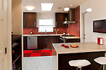 Red tiles provide a burst of color in this bold, contemporary kitchen remodel.
