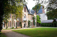 The gothic windows of the chateau are highlighted in red brick and the property has a slate roof