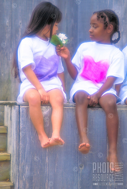 Two young girls, African American and Japanese, smell a flower.