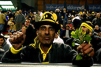 """A Mizrahi ((Jews who came from Asia and Africa) Beitar Jerusalem soccer fan draped in the team's black-and-yellow colours support his team during the match for the league against Hapoel Tel Aviv in the Jerusalem stadium """"Tedy"""". Hapel Tel Aviv is considered by Betar fans  the worst enemy in the league which represents the Ashkenazy (European born) lefty club.  Beitar won the match 2 -1. Beitar Jerusalem FC was founded in the 1930's by the right-wing Revisionist Zionist movement, which later formed the Israeli Likud political party, during the British Mandate rule over Palestine. The chanting of the club is racist and mainly against Arabs. The team is the only one in the Israeli league to have never had an Arab player. Beitar is seen as the right wing and Mizrahi  club. Photo by Quique Kierszenbaum"""
