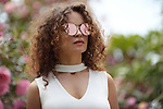 Fashion portrait of a beautiful young stylish woman wearing cat eye shaped mirror sunglasses and a white v-neck open cleavage top in outdoor summer scenery Image © MaximImages, License at https://www.maximimages.com