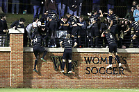 WINSTON-SALEM, NC - NOVEMBER 24: Machop Chol #21 of Wake Forest University climbs the wall with teammates to celebrate with fans after scoring a goal during a game between Maryland and Wake Forest at W. Dennie Spry Stadium on November 24, 2019 in Winston-Salem, North Carolina.