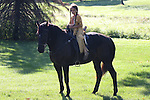 A young Native American Indian Lakota Sioux boy riding a black horse