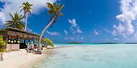 Paradisiac white sand beach bungalow under coconut palm trees, in the turquoise lagoon of Rangiroa atoll, Tuamotus archipelago, French Polynesia