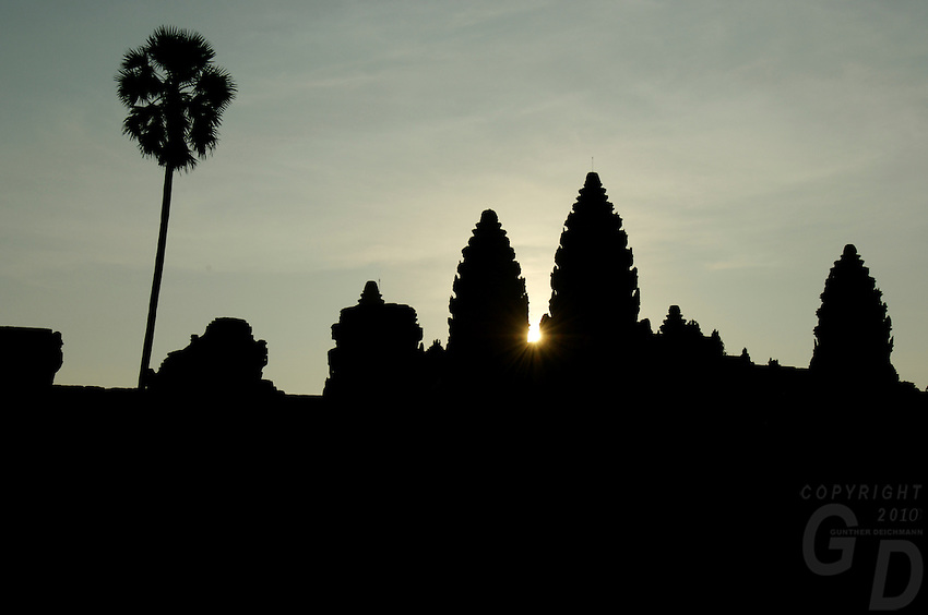 ANGKOR WAT AT SUNRISE, the first rays of light breaking at the temple towers.Siam Reap,Cambodia