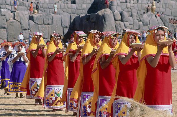 Peru, Cusco Department, Sacsayhuaman, Parade Of Women Offering Food At Inti Raymi. Inca Walls Behind.