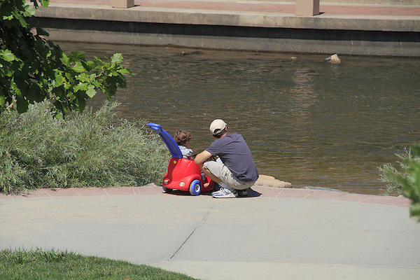 Father with toddler in baby stroller stopping along a stream in Denver, Colorado. .  John offers private photo tours in Denver, Boulder and throughout Colorado. Year-round Colorado photo tours.