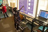 MR / Schenectady, NY. Zoller Elementary School (urban public school). Kindergarten inclusion classroom. Student (girl, 5) signs herself in for the day on digital whiteboard set up with attendance taking software. Student (boy, 6, African American & Puerto Rican American) watches. MR: Nor2, Car38. ID: AM-gKw. © Ellen B. Senisi.