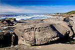 """Viewpoint on Yachts Beach, Yachats, Oregon.  Yachats is a coastal city in Lincoln County, Oregon.  The name is derived from the Native American Siletz word for """"Foot of the Mountain"""".  Yachats State Recreation Area 804 Trail.  Eroded rock.  Young woman watches ocean."""