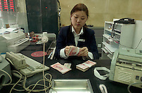 A bank teller counts money in a branch of the Industrial and Commercial Bank of China bank in Beijing, China..