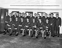 June 20th 1966, Wearing their World Cup uniform - dark grey suit, team tie, white shirt and black shoes - members of England's World Cup soccer squad and officials are pictured at the London Hilton Hotel, Park Lane, tonight (Monday) when they were guests of honor at a boxing dinner of the Anglo-American Sporting Club.  Left to right: Standing - Ron Flowers (Wolves), Alan Ball (Blackpool), Norman Hunter (Leeds United), unidentified, Martin Peters (West Ham United), John Connelly (Manchester United), Jimmy Armfield (Blackpool), Norbert Stiles (Manchester United), Geoff Hurst (West Ham United), Roger Hunt (Liverpool), Bobby Charlton (Manchester United), George Rastham (Arsenal), Bobby Moore (West Ham), the England captain, George Cohen (Fulham), Ian Callaghan (Liverpool), Harold Shepherdson (trainer) and Alf Ramsey (manager.  Seated - Gerry Byrne (Liverpool), Jackie Charlton (Leeds United), Ron Springett (Sheffield Wednesday), Terry paine (Southampton), Ray Wilson (Everton), Peter Bonetti (Chelsea) and Gordon Banks (Leicester City) - June 20th 1966