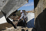 A Palestinian boy checks debris of houses destroyed during an Israeli air strike, near the Nuseirat refugee camp in central Gaza Strip on Jan. 2, 2011. Photo by Ashraf Amra