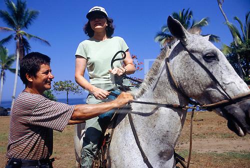 Marenco, Osa Peninsula, Costa Rica. Tourist on horseback with a guide on the beach.