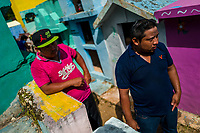 """Mayan peasants participate in the bone cleansing ritual at the cemetery in Pomuch, Mexico, 27 October 2019. Every year on the Day of the Dead, people of Pomuch, a small Mayan community in the south of Mexico, visit the cemetery to take part in a pre-Hispanic tradition of cleaning of bones of their departed relatives (""""Limpia de huesos""""). People who die in Pomuch are firstly buried for three years in an above-ground tomb then the dried-up bodies are taken out, bones are separated, wrapped in a decorated cloth, put into a wooden crate, and placed on display among flowers for veneration."""