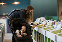 Rachel Sabatini selects books with her son Cooper, 3, and daughter Maisyn, 1, Monday, February 22, 2021, inside the preschool area of the Fayetteville Public Library's new expanded area in Fayetteville. The newly expanded library reopened last month with some sections unavailable to the public because of the covid-19 pandemic. Check out nwaonline.com/210223Daily/ and nwadg.com/photos for a photo gallery.<br /> (NWA Democrat-Gazette/David Gottschalk)