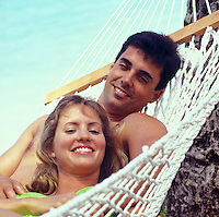 Young couple in hammock near beach