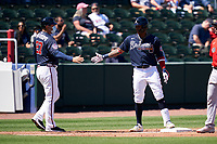Atlanta Braves third base coach Matt Tuiasosopo (27) congratulates Cristian Pache (14) after hitting a triple during a Major League Spring Training game against the Boston Red Sox on March 7, 2021 at CoolToday Park in North Port, Florida.  (Mike Janes/Four Seam Images)